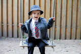 Boy with a tie on a swing