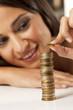 happy attractive girl arrange the coins in column