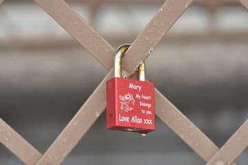 Love padlock tied to a fence