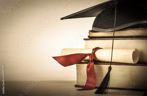 Leinwanddruck Bild Graduation Scroll and Book Stack