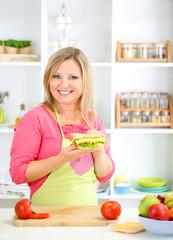 Happy smiling woman in kitchen preparing  sandwich