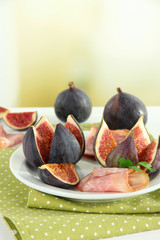 Tasty figs with ham on table
