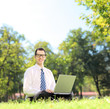 Young businessman sitting on a grass and working on a laptop