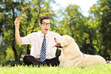 Male sitting on a grass and playing with dog in a park