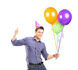Male with party hat holding balloons and giving thumb up