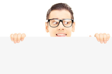 Scared young male with glasses hiding behind a panel