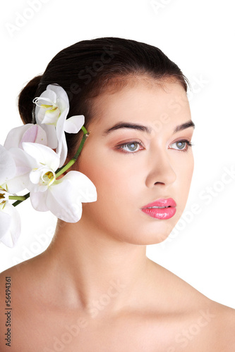 Portrait of beautiful young woman with orchid flower