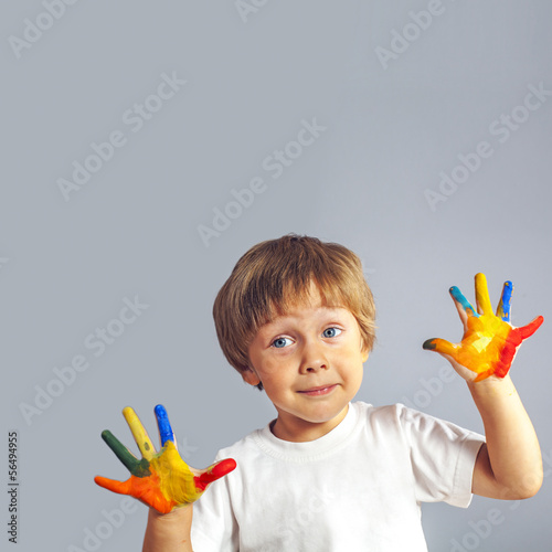 boy with hands painted in colorful paints