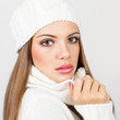 Gorgeous young woman with white winter hat and scarf