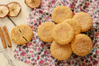 Apple cookies powdered with sugar and cinnamon on wooden backgro