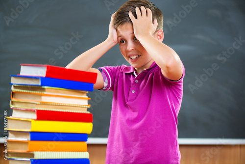 Adorable schoolboy with stack of books