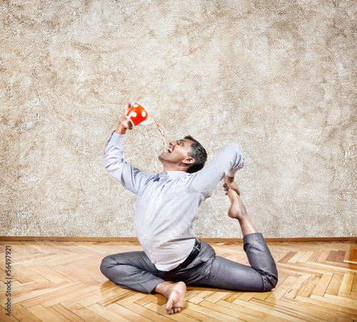 Businessman drinking tea in yoga pose