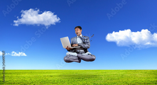 Businessman levitating with laptop