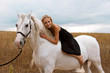 girl in the black dress is riding on horse