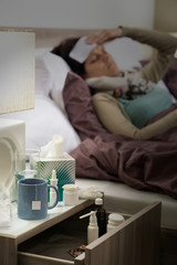 Flu medicines on bedside table ill woman
