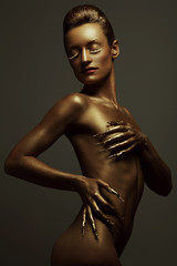 Golden statue of Valkyrie concept. Arty portrait of golden woman