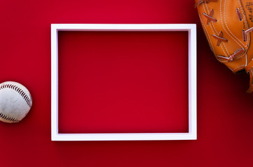 empty picture frame on a red wall with baseball equipment
