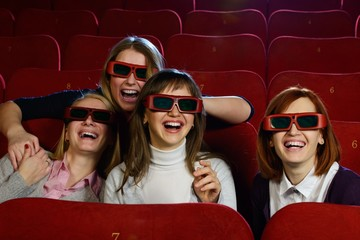 Group of excited young girls watching movie in cinema