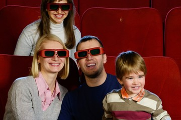 Happy young family in 3D glasses watching movie in cinema
