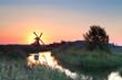 sunrise with sun behind Dutch windmill