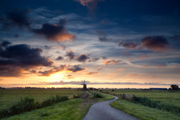 beautiful sunrise over Dutch windmill and pasture
