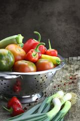 Vintage moody background with vegetables in colander