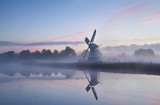 charming Dutch windmill in morning mist at sunrise