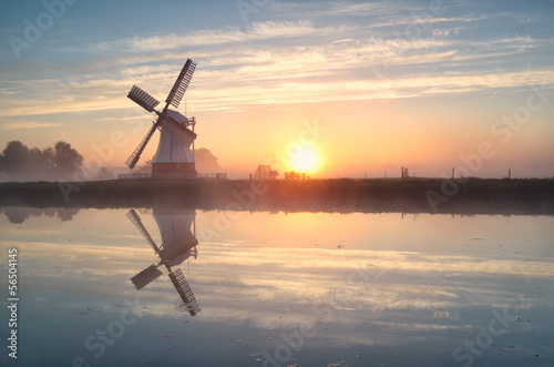 Plagát Dutch windmill reflected in river at sunrise
