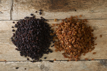 Golden and black raisins over wooden table