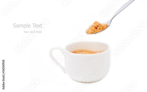 a cup of espresso coffee and spoon of brown sugar