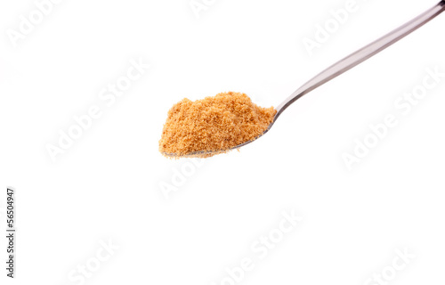 a spoon of brown sugar isolated on white