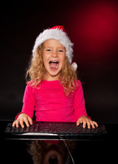 Happy girl in christmas hat with keybard
