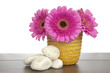 Pink Gerbera in yellow basket and white rocks