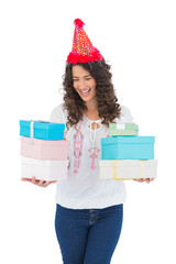 Happy casual brunette with party hat holding presents