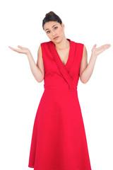 Hesitant elegant brunette in red dress posing