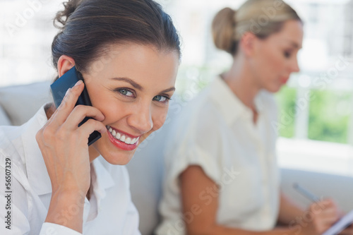 Businesswoman having a call while her colleague writing