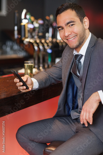 Cheerful businessman sending a text while having a drink
