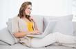 Thoughtful cute woman using laptop