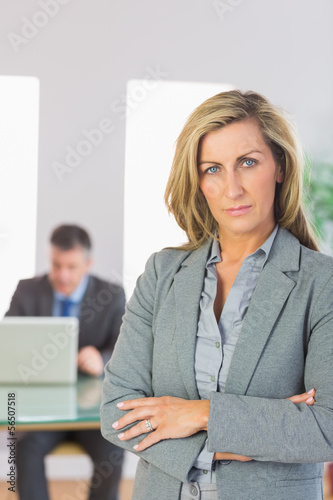 Serious businesswoman looking at camera crossed arms with a busi