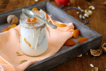 jar of fresh yogurt with nuts and apricots on an old tray