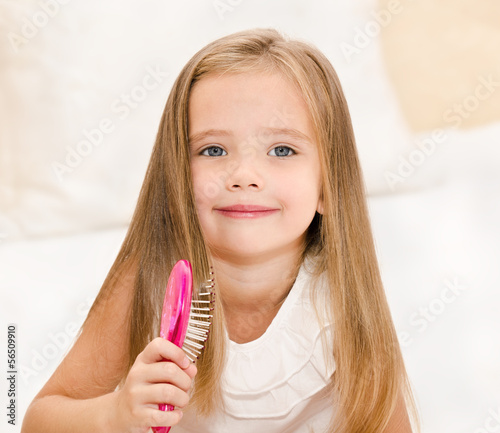 Portrait of smiling little girl brushing her hair