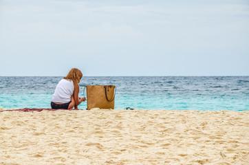 A girl sit on the beach at Nang Yuan island. Thailand