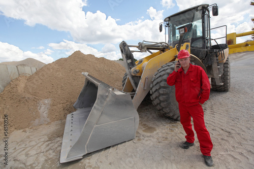 worker in red uniform on phone, buldozer in background