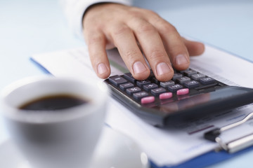 Mans hand working with a calculator