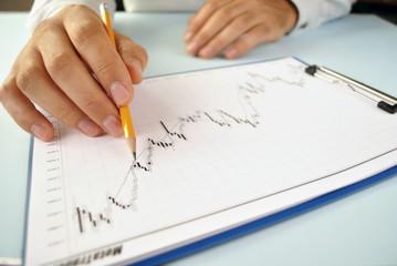 Man analysing an upward trending graph