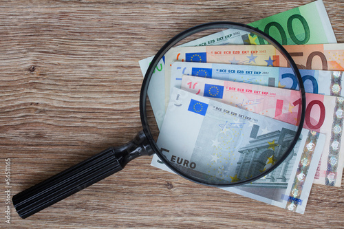 euro banknotes under magnifying glass
