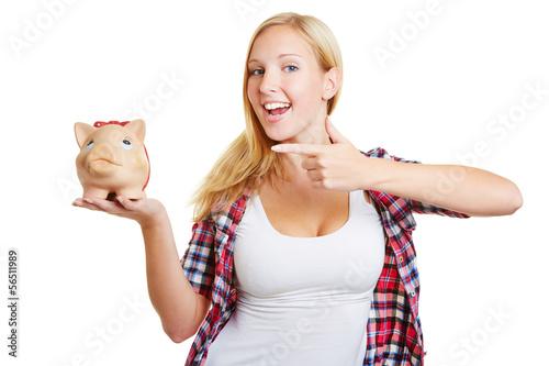 Frau zeigt mit Finger auf Sparschwein