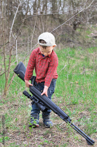 Small boy lugging a sporting rifle