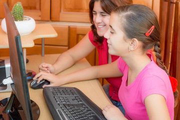 Happy latin girl and her young mother working on a computer