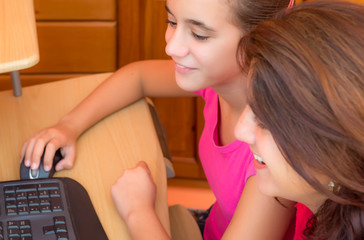 Young latin girl and her  mother working on a computer